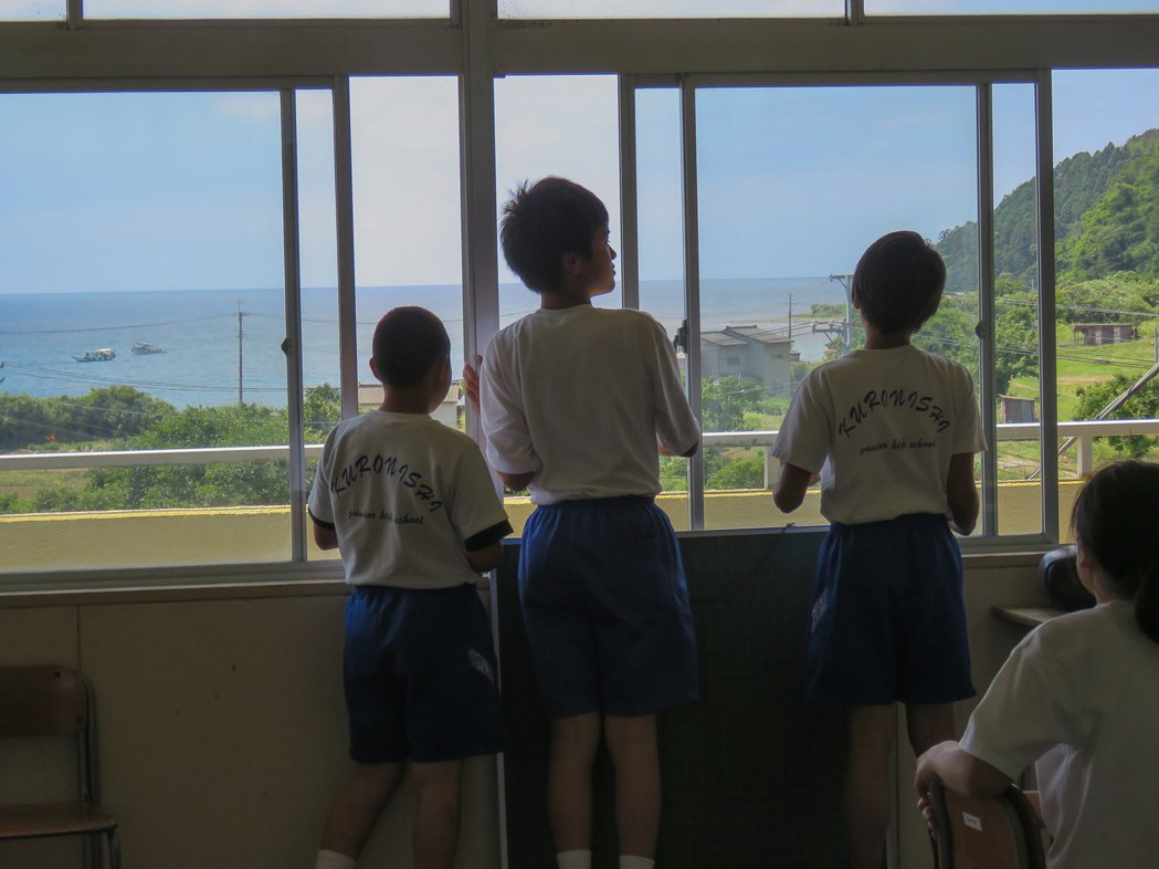 從粟島中學的教室望出去就是大海,下課時間三位留學生眺望美景。記者雷光涵/攝影