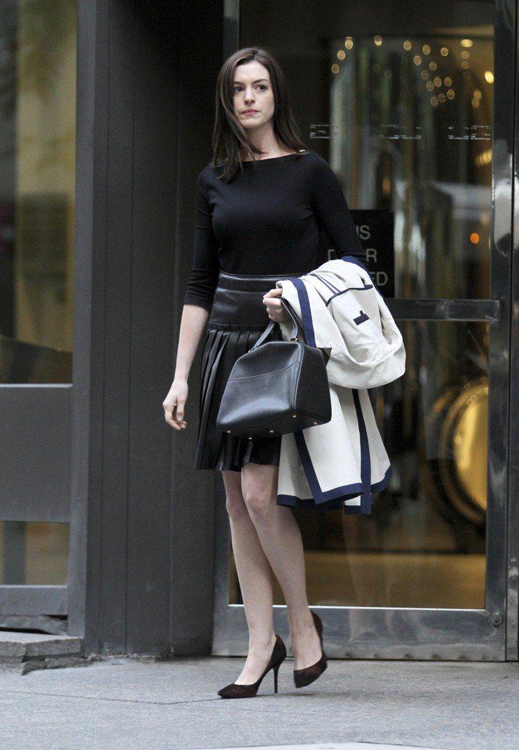 一身黑是女強人絕不會出錯的裝扮,安海瑟薇以亮皮黑裙為黑增添質感。圖/達志影像