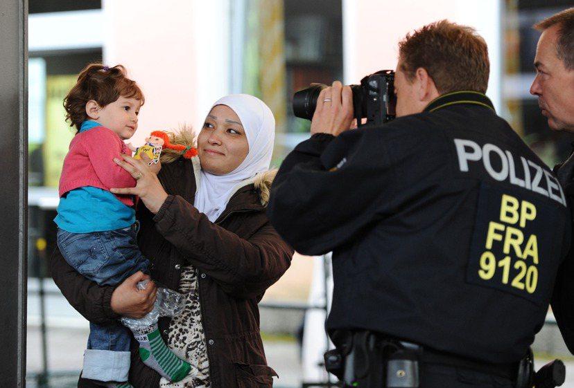 德國警察在難民登記處幫一名敘利亞女童拍照建檔。 圖/歐新社