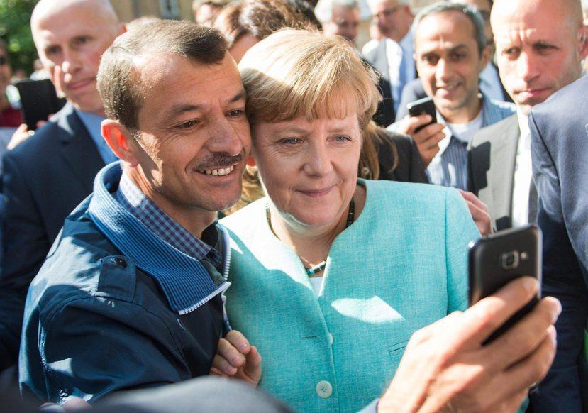 梅克爾探訪難民收容中心時,與一名來自敘利亞的難民自拍。 圖/ 歐新社
