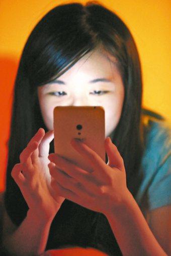 在暗處看手機會造成眼睛傷害嗎? 報系資料照
