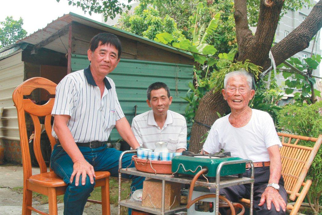 一百零四歲的鄰長黃德成(右起),跟兒子黃昆山、村長鍾文一喝茶聊天。 記者卜敏...