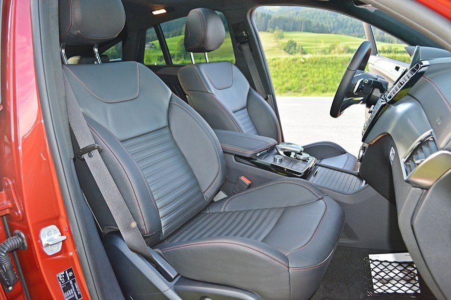 跑車式樣的真皮座椅版型繁複,左右和腿部有很好的包覆性。