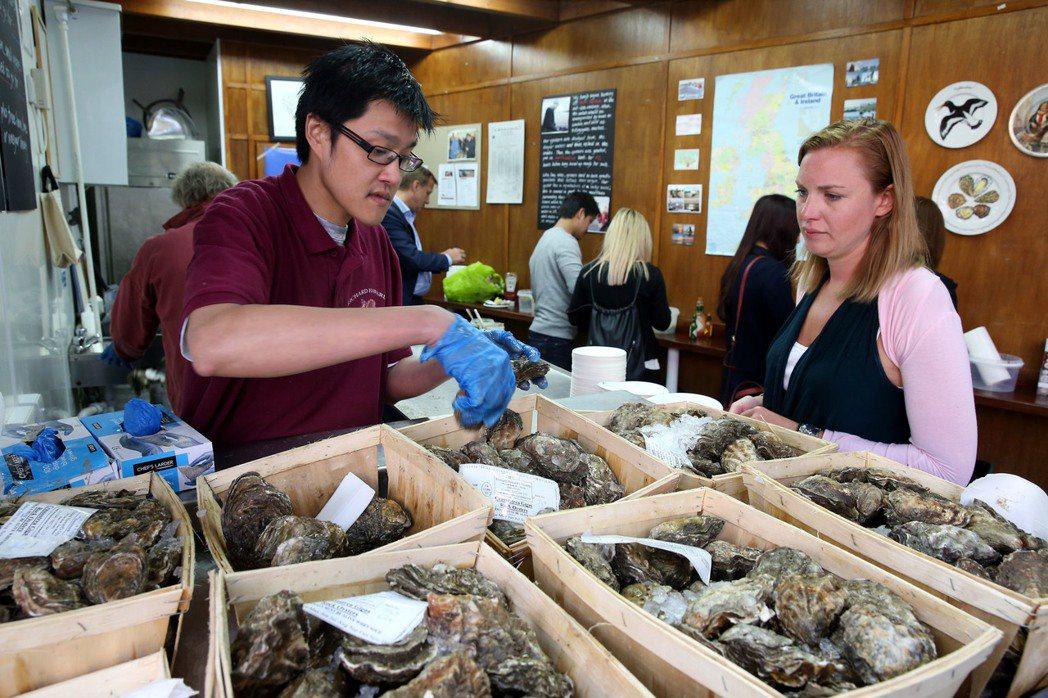 英國倫敦千年波羅市場,來自台灣的移民許博源(左)在市場賣牡犡,生意超好。 特派記...
