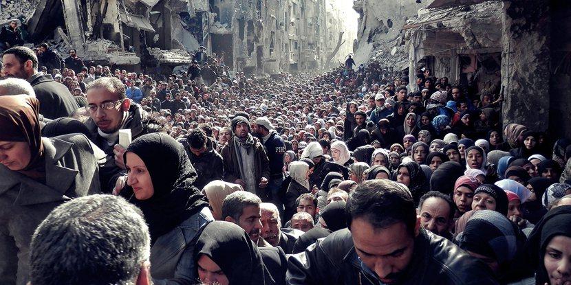(資料圖片)2014年大馬士革,受到戰火摧殘的雅爾矛克難民營,居民們正在等待糧食...