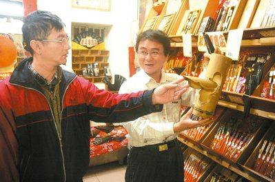 蔡享潤(右)在故鄉開了一家柑仔店,專賣各種傳統工藝或童玩,他細心向客人說明古早器...
