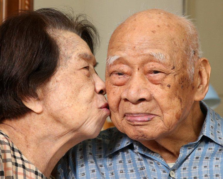 百歲人瑞夫妻檔黃奕培(右)與黃王勝玉(左),黃王勝玉害羞地親吻丈夫黃奕培。 ...