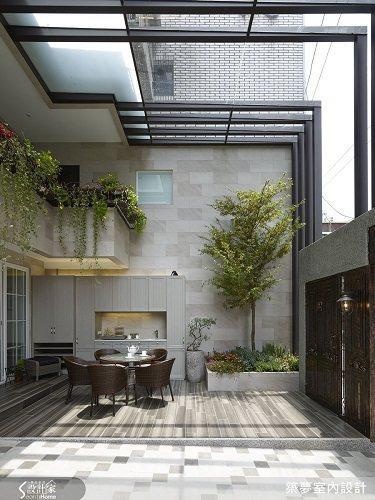 以木紋磚鋪滿庭院地板,其中也保留了對女主人來說紀念意義深重的兩棵樹,讓庭院造景自...