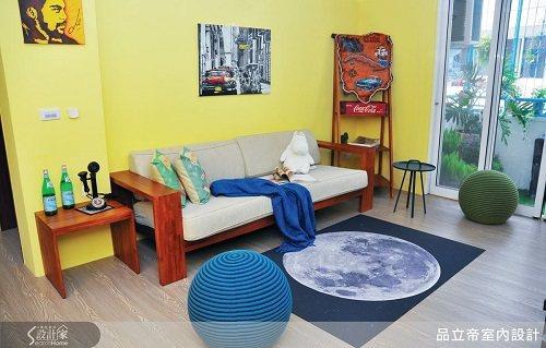 客廳以鮮明的藍、黃及原木色為主色調,簡單的一字型沙發、圓滾滾的坐墊及色彩飽和的牆...