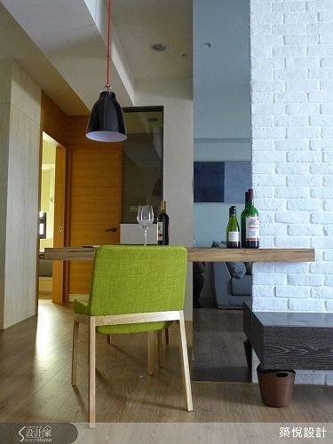 設計師利用電視牆作為客廳與廚房的隔牆,並且在牆面側邊嵌入餐桌,開放式的餐廳設計因...