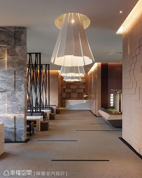 ▲造型燈具引領著前往櫃台的視覺焦點,同時讓廊道兩側的石材紋理獲得最佳的映照。