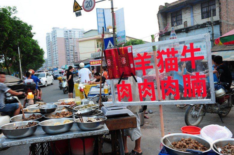 中國廣西玉林市區南橋市場的一家賣肉攤把「狗」肉的狗字遮住。 圖/新華社