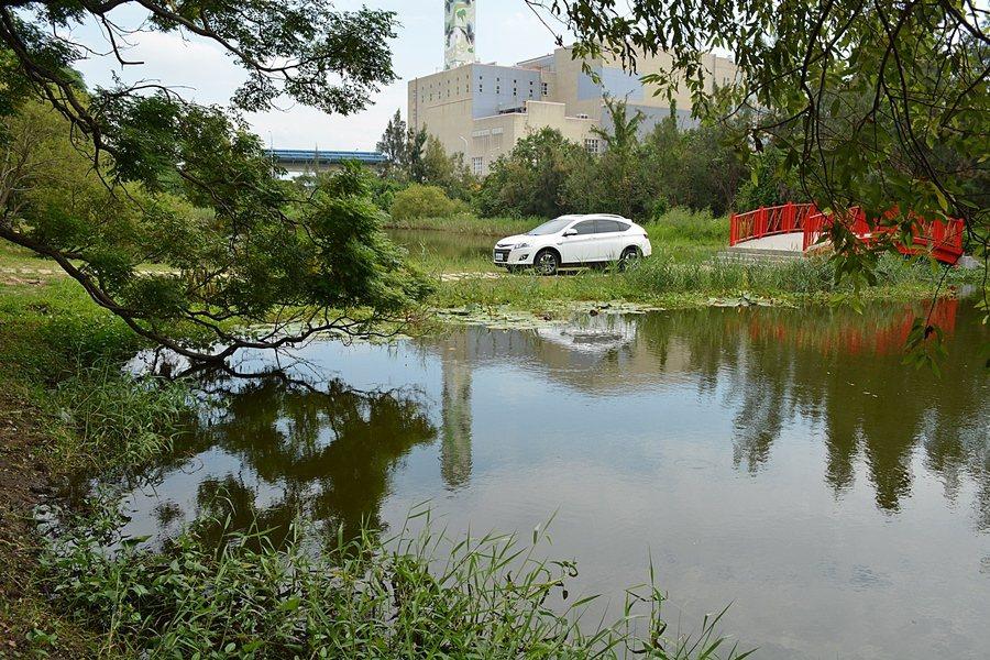 白色的U6 TURBO休旅車停在中港溪濕地水岸邊,我們在對面的樹蔭下按下快門,輕...