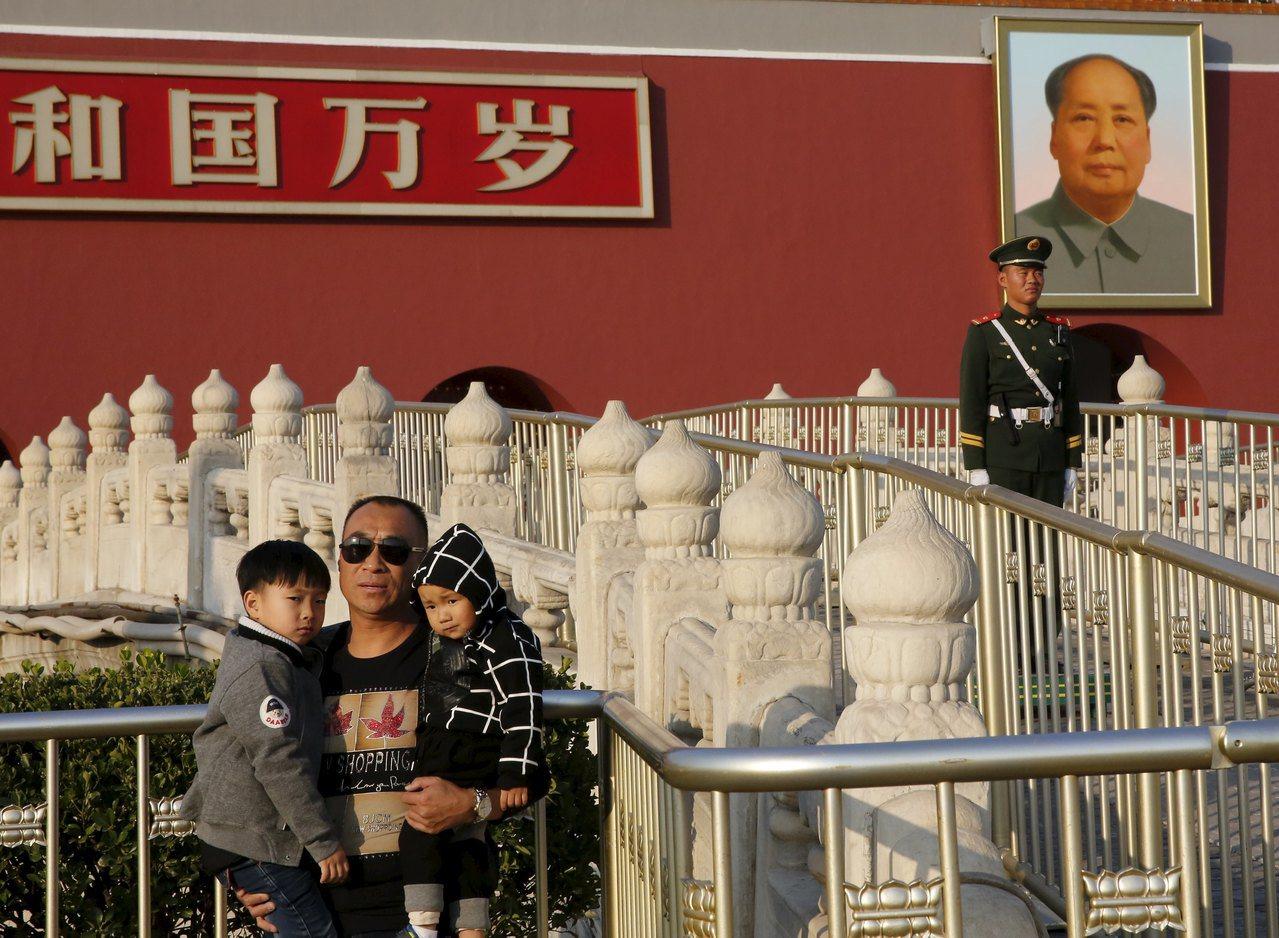 北京市近5年來常住人口成長數量及成長速度均呈現不斷下降。圖為一名北京民眾抱著兩名...