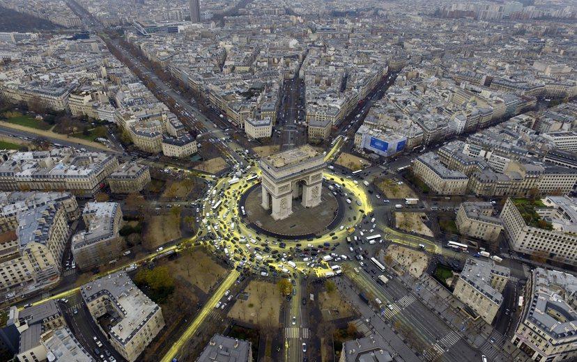 星期五「綠色和平組織」以巴黎凱旋門為中心,在周圍的道路以放射狀方式,潑灑黃色的生...