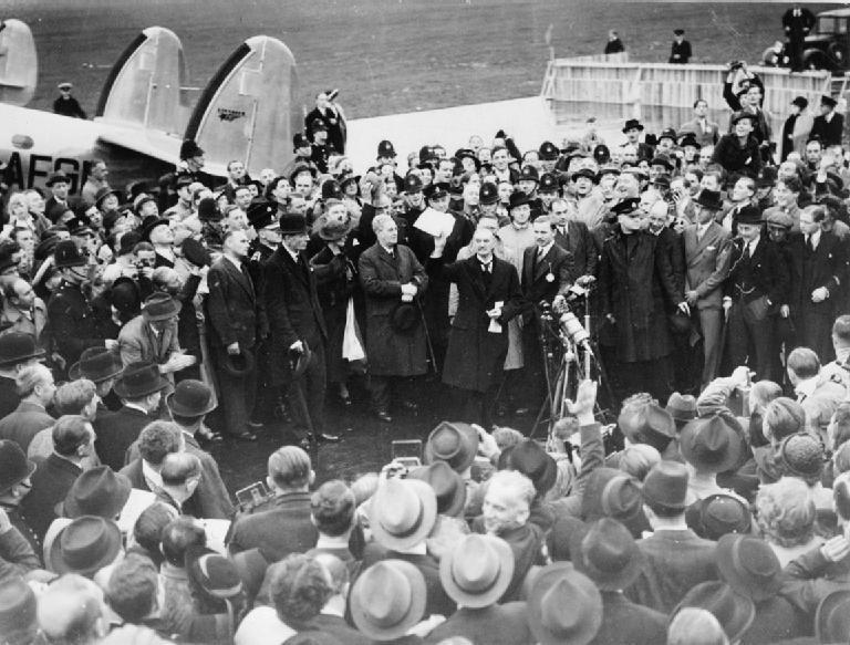 1938年9月30日,英國首相張伯倫在機場對群眾揮舞著與希特勒簽署的和平協定。 ...