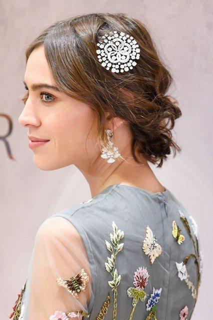 蓬松的頭髮挽在腦後在側面搭配以bling-bling的花朵形狀髮飾與衣服上的花朵...