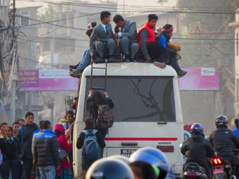 能源危機造成大眾運輸班次縮減,民眾只能上演「特技」坐上車頂。 圖/作者謝承佑提供
