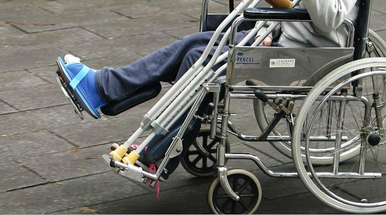 打石膏坐輪椅示意圖。報系資料照