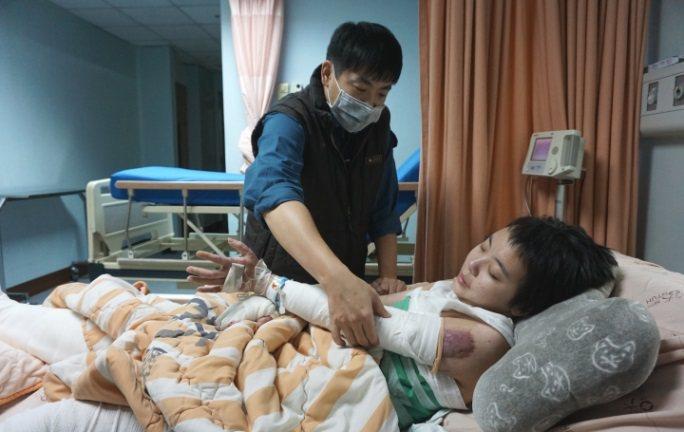 哥哥輕拍伃均手術後的手臂止癢,持續拍著 攝影/江佩津
