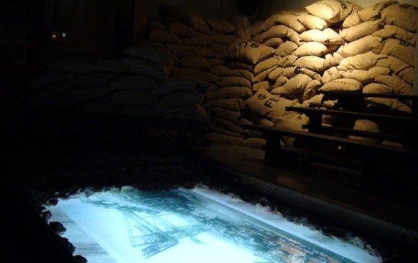 跨進舊事倉庫,糖包堆疊成舊產業印記,地洞影片在舊鐵軌的時光縫隙中播放。