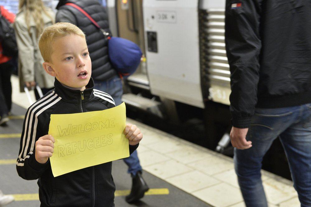 去年九月一名瑞典小男孩在斯德哥爾摩中央車站,舉著歡迎難民的牌子。 (圖/歐新...