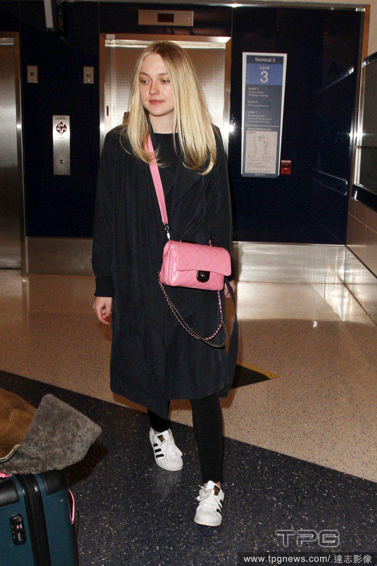 達柯塔芬妮用長版風衣搭休閒運動鞋,配香奈兒早春粉紅包款俏麗瀟灑。圖/達志影像