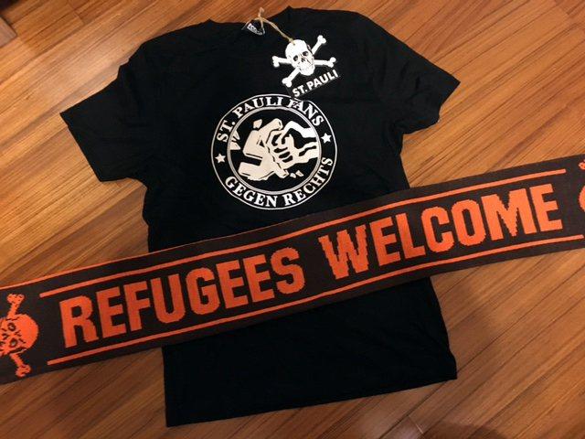 去年開始,聖保利官方商店裡賣著「歡迎難民」(Refugees Welcome)的...
