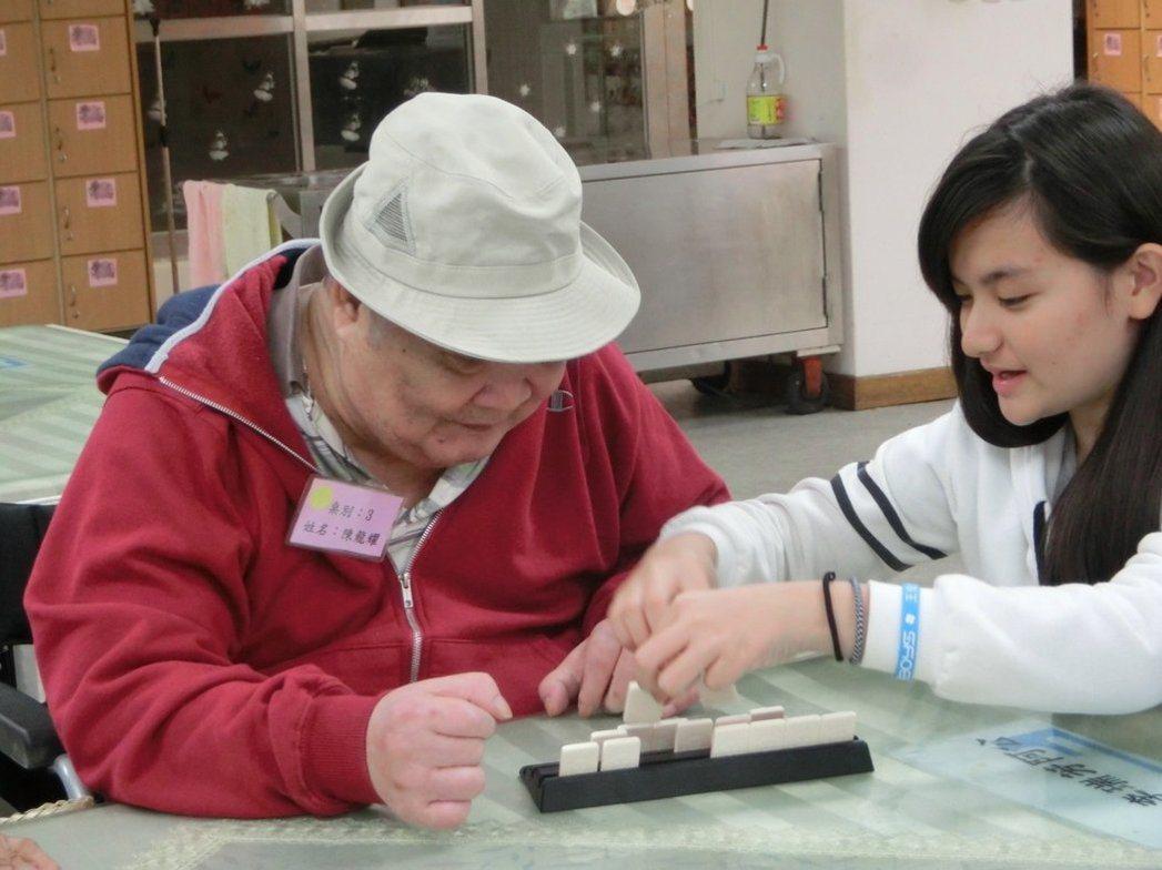 南區老人之家少教所青少年帶領阿公阿嬤玩桌遊,提早過新年。記者蕭雅娟/攝影