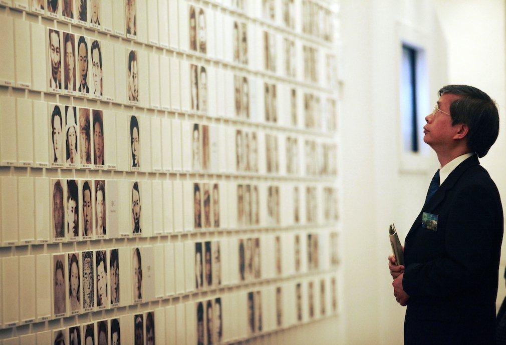 在二二八國家紀念館裡, 駐足於受難者照片前的男人。 圖/路透社