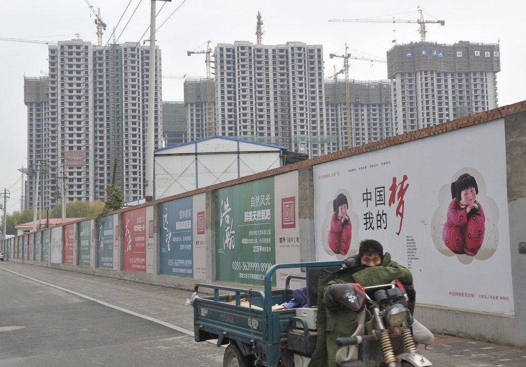 進城買房是許多農村人的夢想,圖為一名山西農民工駕駛三輪車途經一處貼有「中國夢」海...