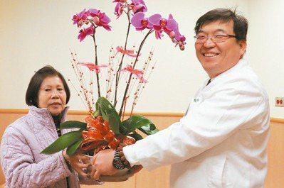 蔡姓婦人(左)接受手術後狀況改善,特地贈花給林英超醫師,表達感謝。 圖/台中慈濟...