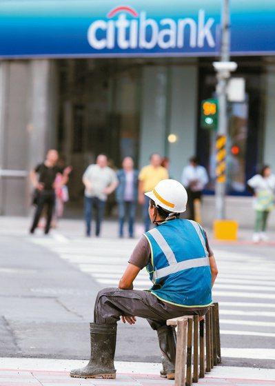 台北街頭一名工人在等待紅綠燈時,把原本扛在肩上的梯子當成椅子,坐在馬路旁休息,與...