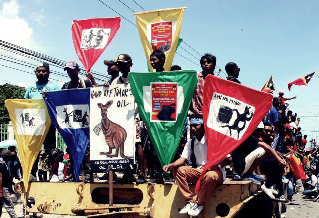 3月23日:包為澳使館的東帝汶民眾,抗議看板上的袋鼠脖子上掛「石油」。 圖/歐新...