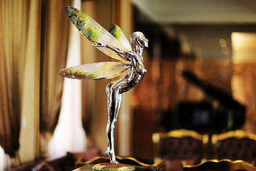 雕塑大師彭光均創作的「展」,利用不銹鋼、琉璃一剛一柔的材質,展露出少女展次飛翔的...