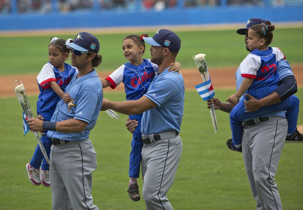 賽前光芒隊球員抱起古巴小孩。 圖/美聯社