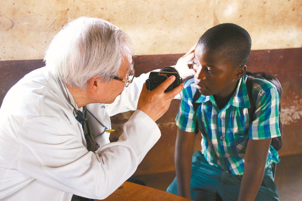 醫師鍾昌宏(左)替眼睛不適的史國孩子檢查。 記者陳雨鑫/攝影