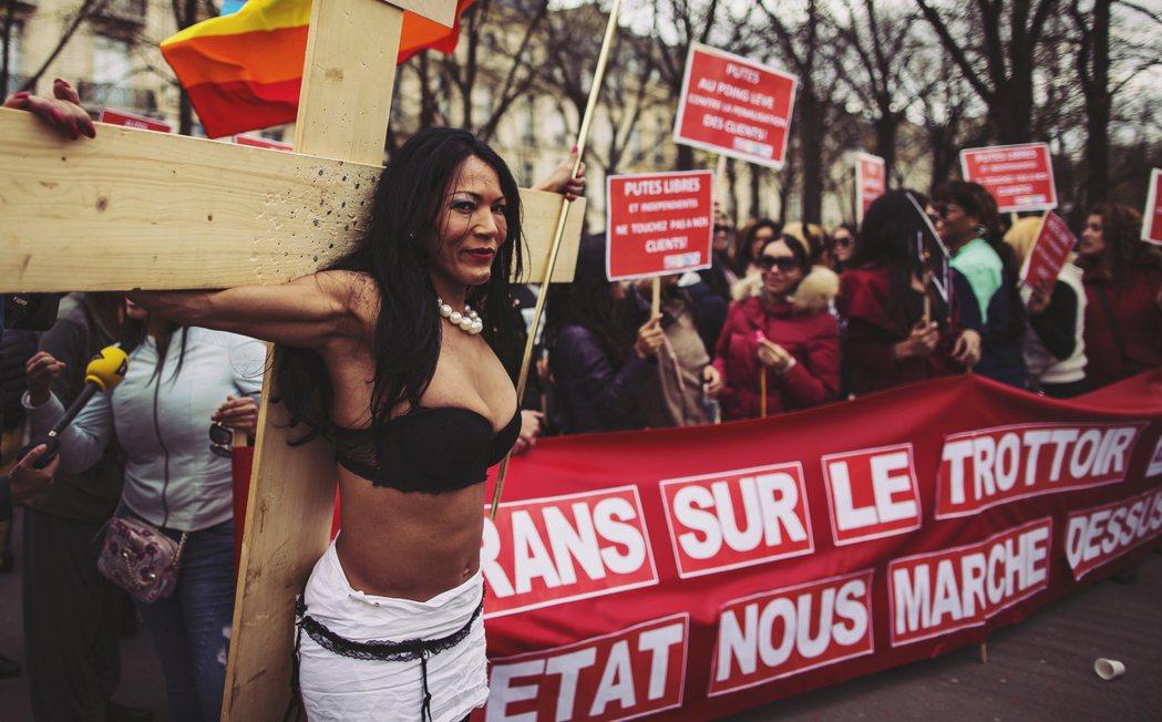 4月7日:再法國國會外抗爭的性工作者,她們扛著十字架、舉著標語「性工作者,揮舞拳...