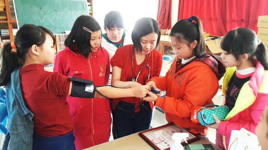 在英國讀醫學系的蔡亭玉(中)帶著聽診器、血壓計,教偏鄉學童如何正確量血壓。圖/南...