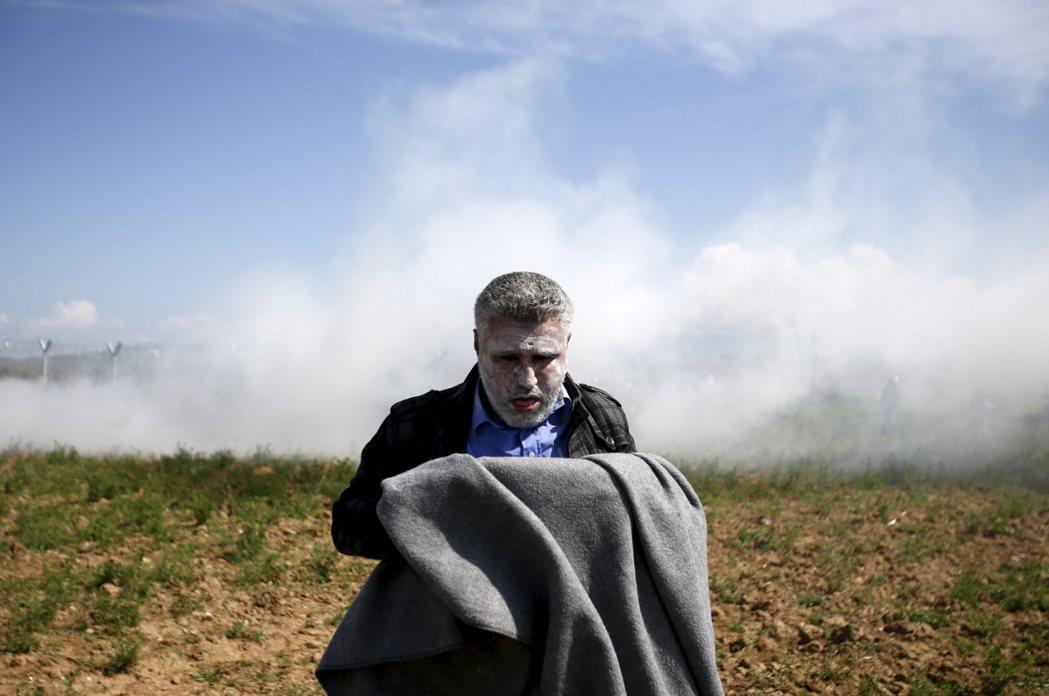 馬其頓與希臘邊境:被催淚彈折騰得灰頭土臉的難民。 圖/路透社