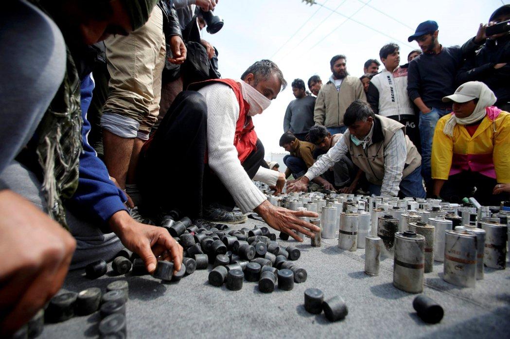 難民向記者展示馬其頓警察所使用的催淚彈殘骸。 圖/路透社