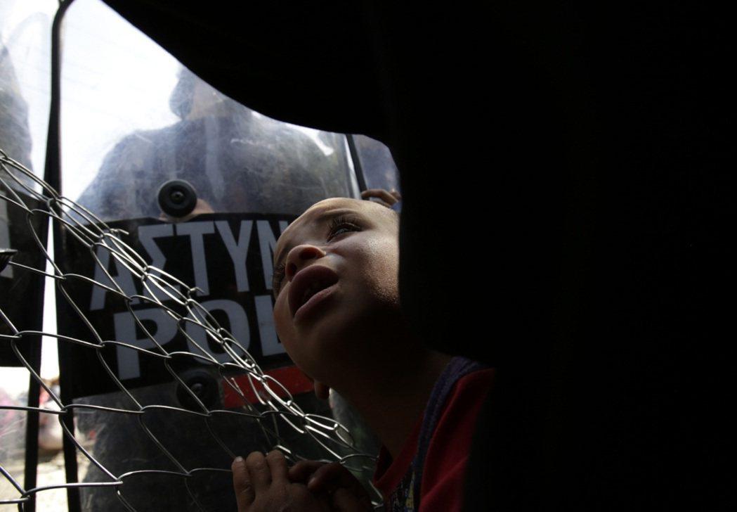 夾在希臘軍警的盾牌中掙扎的難民兒童。 圖/美聯社