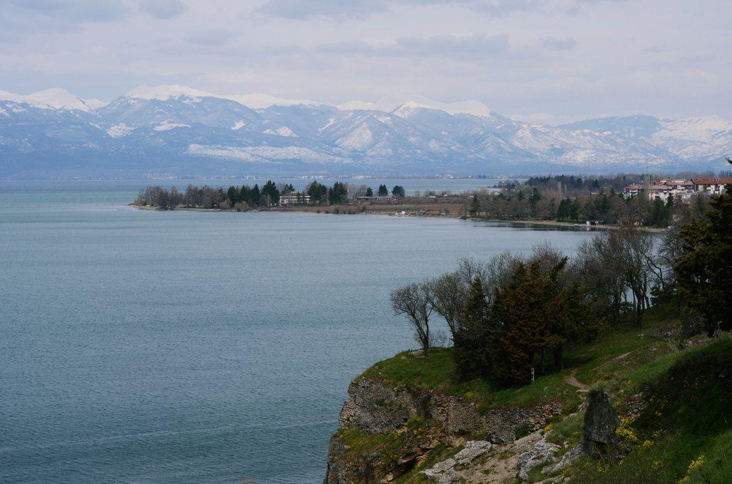 奧赫里德湖(Lake Ohrid)貼著公路向外鋪陳,湖面上墨黑的液體,和遠方山稜...