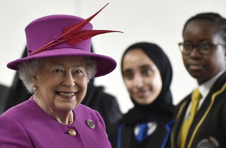 酒紅羽飾的帽飾,成為紫色衣裝的點睛表現。圖/取自www.ibtimes.com