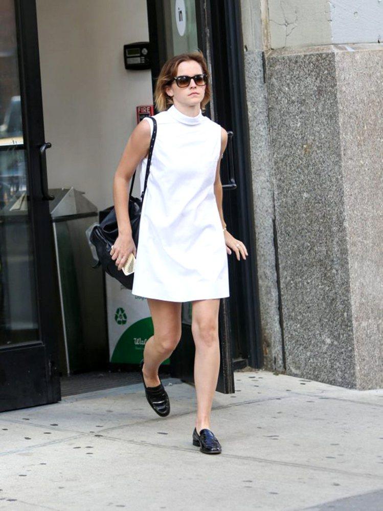 艾瑪華森選擇高領的白色無袖洋裝,六○年代的A字線條不只修身,搭上黑色樂福鞋保留一...