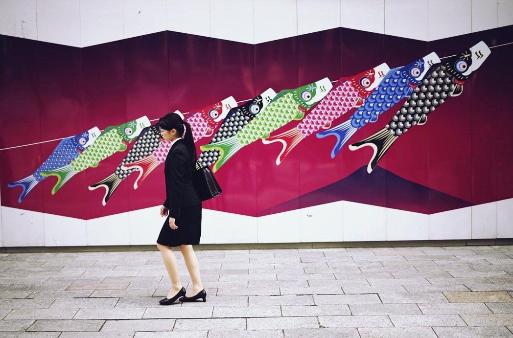 5月4日:東京街頭,一名經過鯉魚旗陣的年輕女性。 圖/美聯社