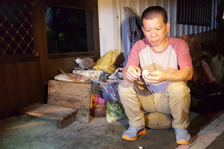 鄭性澤在家門口剝著家人預先準備的鴨蛋象徵「脫殼」。 圖/聯合報系資料照片