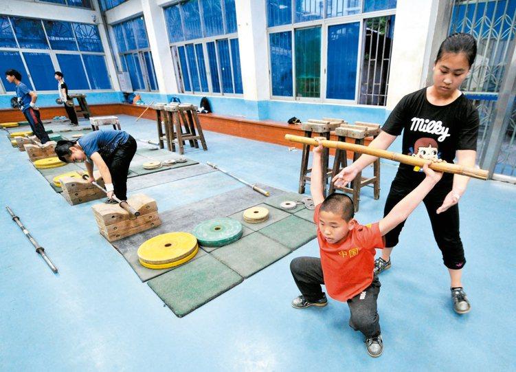 大陸公布體育發展「十三五」規劃。圖為福建省龍岩體育運動學校學生練習舉重。 中新社