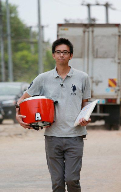 緬甸稻農蔡磊堅抱著大同電鍋推銷台灣米。 記者黃義書/攝影
