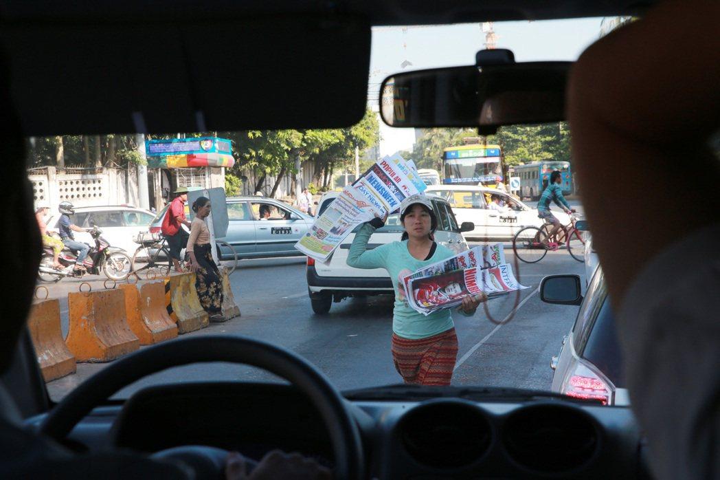 仰光街頭兜售報紙的婦女。 記者黃義書/攝影